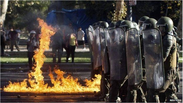 Riot troops march past fire from petrol bomb