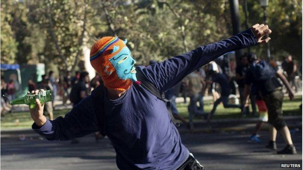 Masked protester in Chile throwing bottle