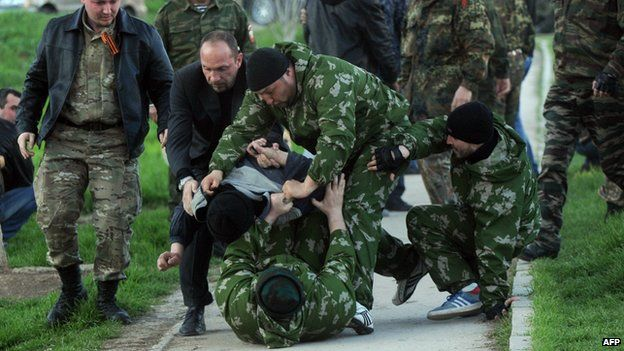Pro-Russian men beat an unknown man during the takeover of the Belbek airbase on Saturday