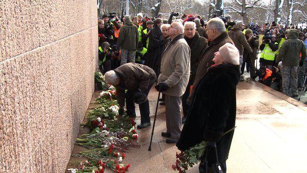 Elderly Latvians lay flowers at a war memorial in Riga