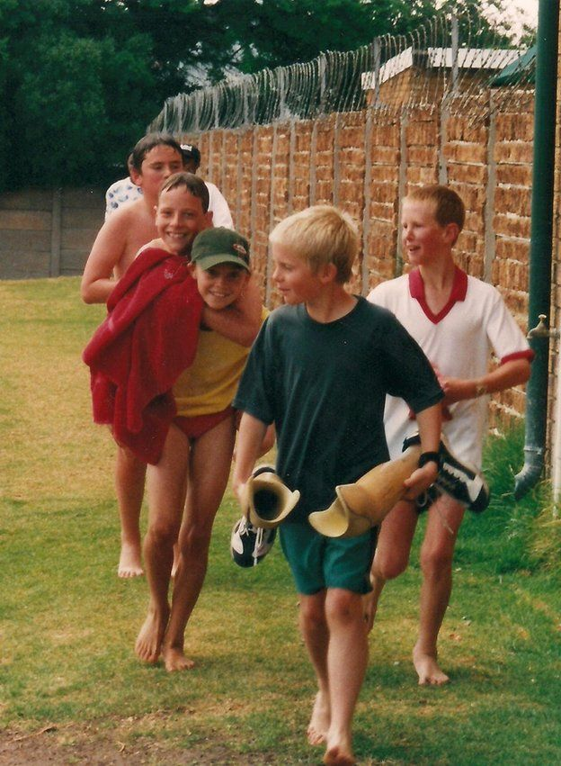 Oscar Pistorius is given a piggy-back by a friend