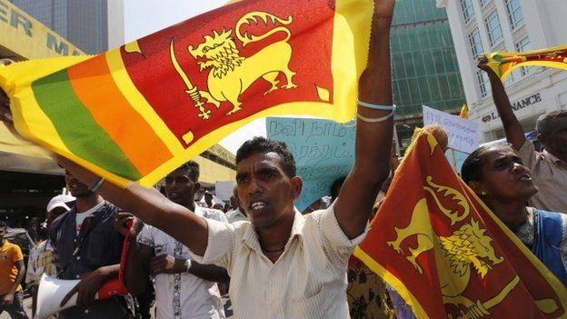 Sri Lankan government supporters from the former northern war zone area wave the national flags and shout protest slogans outside the U.S. embassy in Colombo, Sri Lanka, Thursday, March 20, 2014
