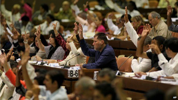 Members of the National Assembly raise their hands to vote during an extraordinary session overhauling their foreign investment law at the National Assembly in Havana, Cuba, on 29 March 2014.