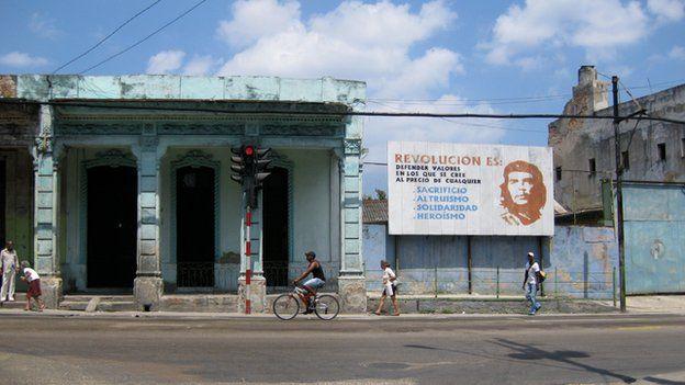 Man and pedestrians walk past a billboard showing Che Guevara