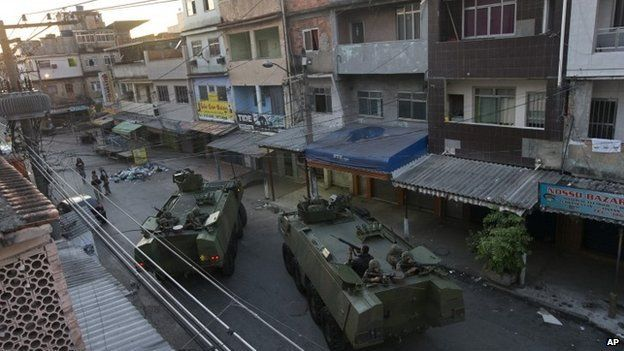 Brazilian soldiers take position during an operation to occupy the Mare slum complex in Rio, 30 March