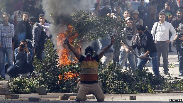 Students supporting the Muslim Brotherhood shout slogans near a bonfire in front of riot police during clashes outside near Egypt's defence ministry headquarters in Cairo on 27 March 2014.