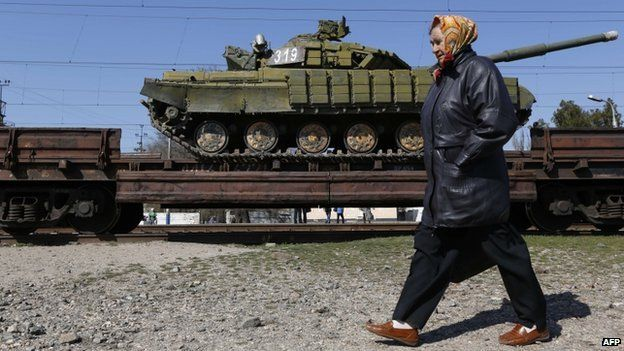 A woman walks past a trainload of Ukrainian tanks near the Crimean capital Simferopol on 31 March 2014