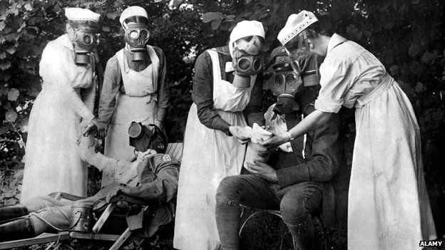 Nurses in gas masks treat soldiers afters a gas attack