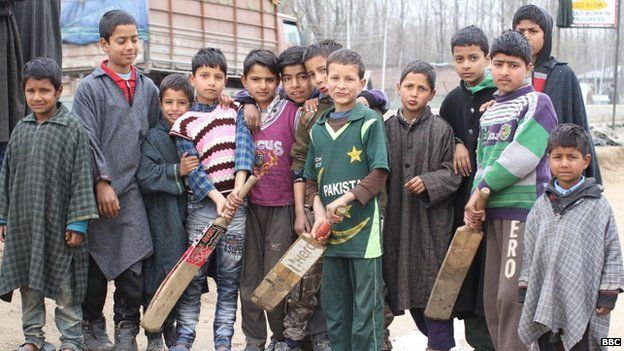 Children playing cricket stop to pose for a picture in the streets of Kashmir
