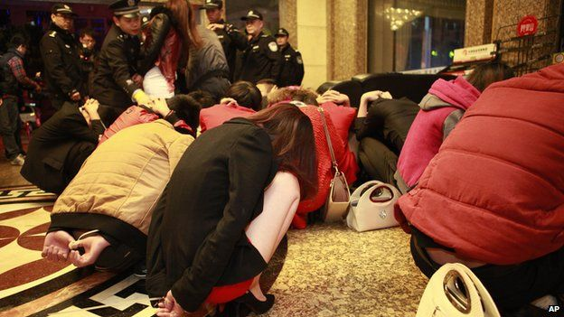 Detained suspects gathered in a lobby during an anti-prostitution raid at a hotel in Dongguan in south China's Guangdong province on 9 February 2014