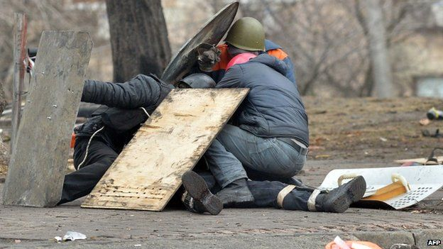 Anti-government protesters shield a wounded demonstrator in Kiev. Photo: 20 February 2014