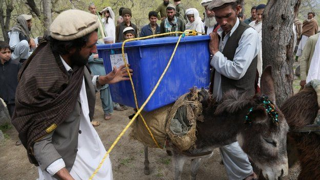 Afghan election workers load ballot boxes and election materials on a donkey to deliver to polling stations in Dara-e-Noor district of Jalalabad, east of Kabul