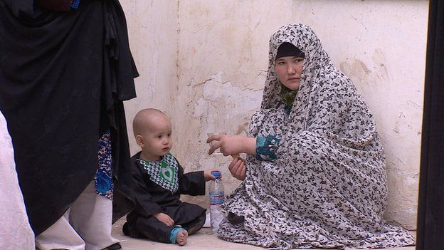 A voter in Mazar-i-Sharif with her child