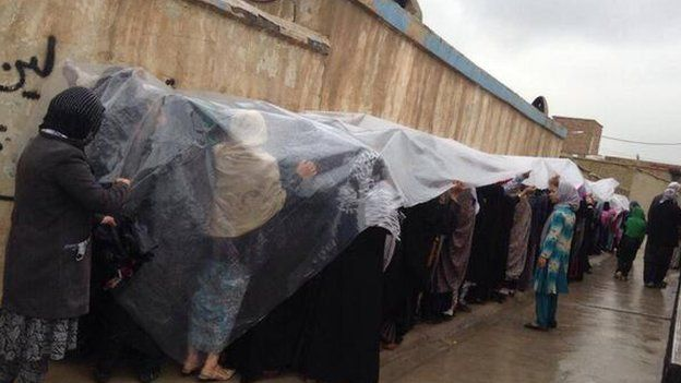 Women voters waiting in line in the rain