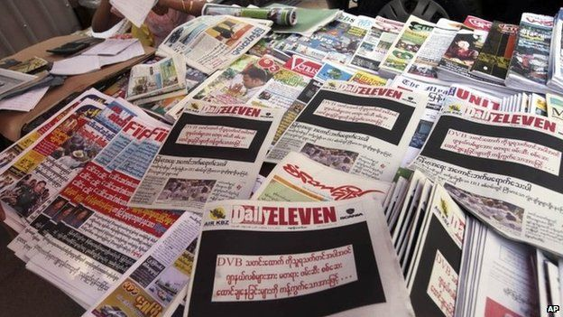 "A vendor sits by local weekly news journals with their front pages printed black with letters saying ""By opposing recent arrest and sentencing of journalists including a video journalist of DVB (Democratic Voice of Burma)"" at a roadside shop Friday, 11 April 2014, in Yangon, Myanmar"