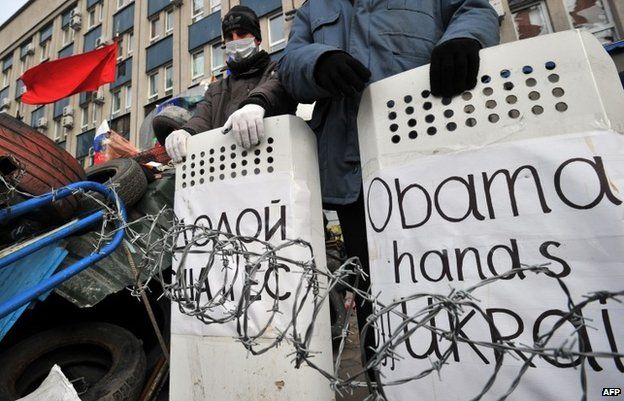 """Po-Russian activists hold shields signed """"Obama hands off Ukraine """"and """"Down with US and EU"""" as they guard a barricade outside the secret service building in the eastern Ukrainian city of Luhansk on April 12,"""