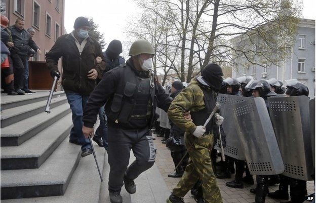 Masked pro-Russian activists leave the regional prosecutor's office was riot police, right, watch them, in Donetsk, April 12