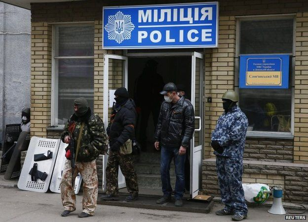 Armed men stand in front of the police headquarters building in Sloviansk, April 12