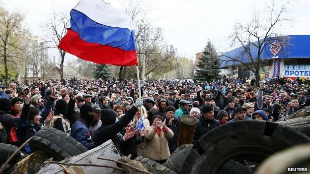 Protesters wave the Russian flag in front of police station in Slaviansk 12/04/2014
