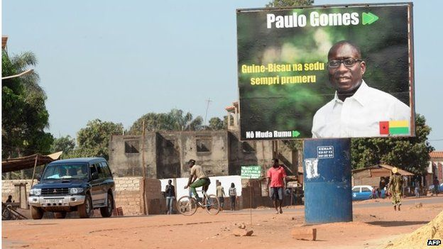 People walk past a campaign poster for presidential candidate Paulo Gomes in a street in Bissau on 11 April
