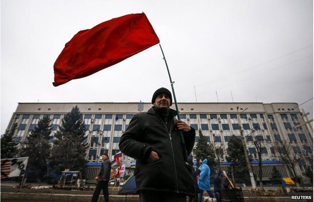 A pro-Russian supporter holds a Soviet flag in front of the seized office of the SBU state security service in Luhansk, in eastern Ukraine April 13