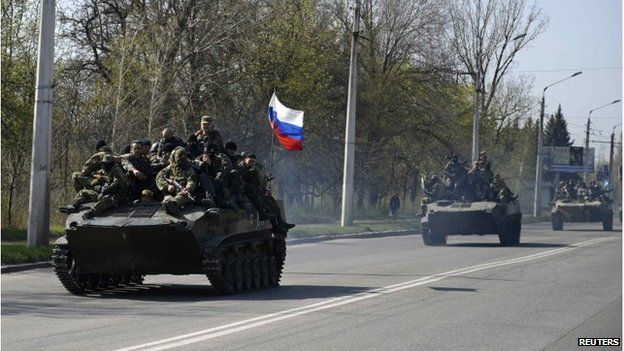 Armed men, wearing black and orange ribbons of St. George - a symbol widely associated with pro-Russia protests - drive an airborne combat vehicle with a Russian flag on top, outside Kramatorsk