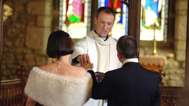 Vicar officiates at church wedding