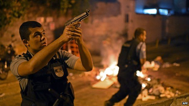 A Brazilian Police Special Forces member takes position during a violent protest in a favela near Copacabana in Rio de Janeiro, Brazil on 22 April 2014