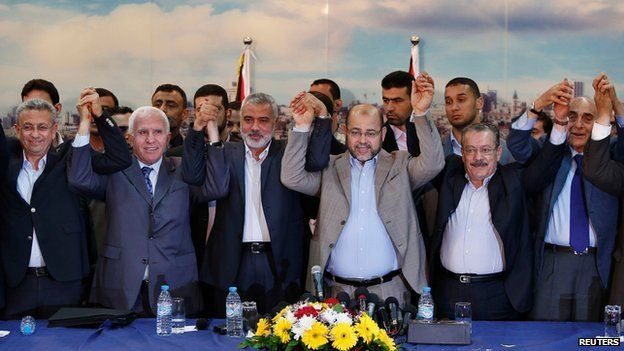 Members from Fatah and Hamas hold hands after announcing reconciliation deal in Gaza City on 23 April 2014