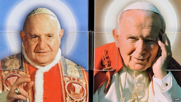 Postcards depicting Pope John XXIII (left) and Pope John Paul II, in a shop in central Rome, 21 April 2014