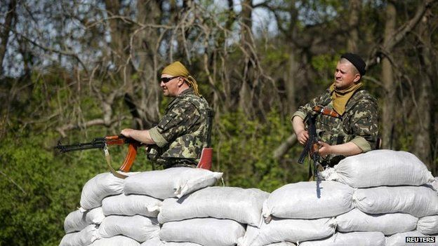 Ukrainian soldiers stand guard at a checkpoint in the village of Malinivka, 24 April