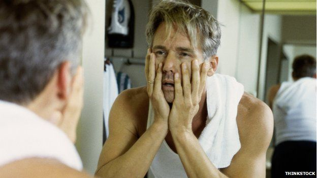 A tired-looking man man looking in the mirror