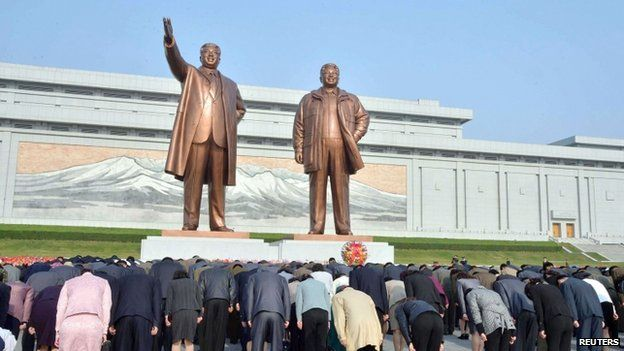 North Koreans bow in front of bronze statues of North Korea's founder Kim Il-sung (L) and late leader Kim Jong-il at Mansudae in Pyongyang, in this photo provided by Kyodo on 25 April 2014, on the 82nd anniversary of the founding of the Korean People's Army