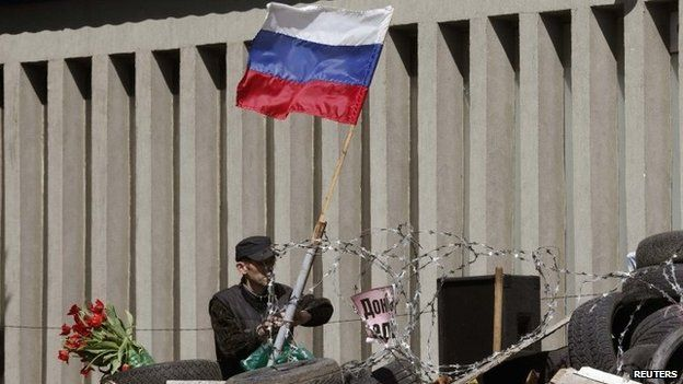 An activist attaches a Russian national flag on the barricades in front of the seized office of the SBU state security service in Luhansk, eastern Ukraine, April 28, 2014