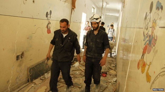 Government staff walk inside a school that was hit by what activists said was an airstrike by forces loyal to Syria's President Bashar al-Assad in Aleppo on 30 April 2014