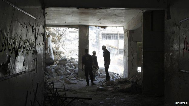 Rescuers watch an excavator operating at Ain Jalout school in what activists say was a Syrian government air strike
