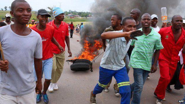 Protesting residents drag burning tyres as they march on the main road leading into the town of Bronkhorstspruit during a protest over poor public service delivery, on 6 February 2014