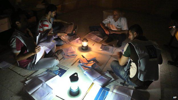 Electoral workers count ballots under lamplight due to a power cut, as polls close at a polling centre in Basra, Iraq's second-largest city
