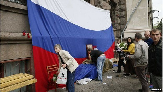 Mourners place flowers by a Russian flag outside the burned building in Odessa (4 May 2014)