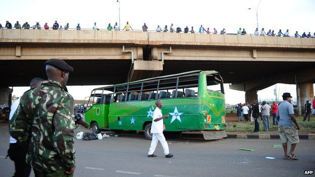 A soldier stands guard near a damaged bus after two explosions hit two buses along Nairobi's Thika road, on 4 May 2014.