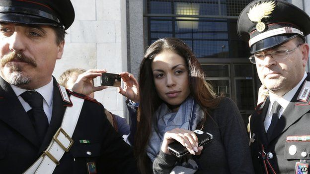 Karima el-Mahroug is escorted outside a Milan court by two Carabinieri police officers after giving her testimony at the trial in Milan (May 2013)
