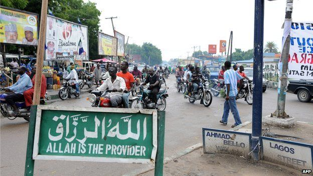 A picture taken on 28 July 2010 shows residents riding past a sign reading 'All is the Provider', both in English and Arabic, in Maiduguri, Nigeria