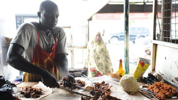A roadside vendor cuts locally prepared barbecue popularly known as suya in Maiduguri, north-eastern Nigeria on 11 May 2012