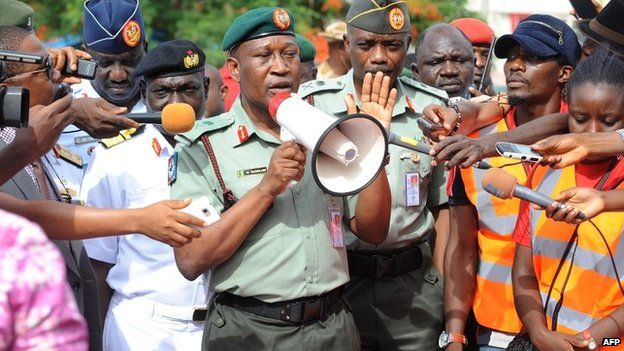 """Defence spokeman Major General Chris Olukolade speaks to a crowd in Abuja protesting over the government's """"indifference"""" to the mass abduction - 6 May 2014"""
