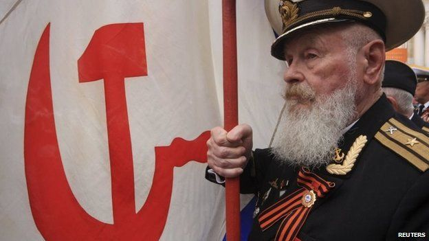 A former Soviet serviceman marches with a Soviet navy flag to mark Victory Day in the Crimean port of Sevastopol May 9
