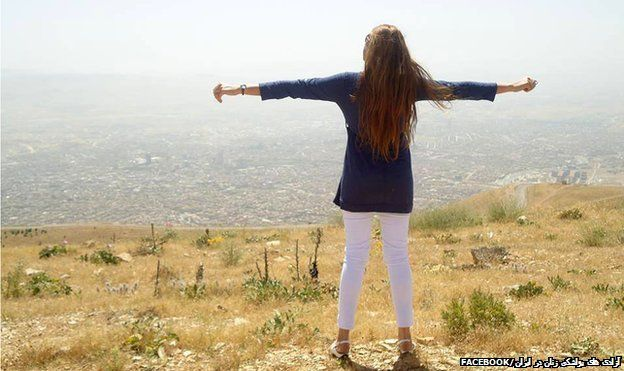 "A woman standing on the top of a hill with her back to the camera and her arms outstretched - one of the images of the ""My Stealthy Freedom"" Facebook page"