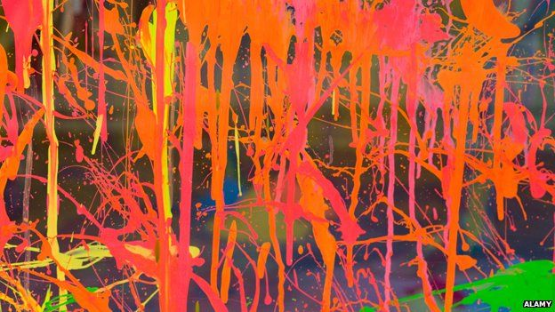 A glass window is splattered with orange and pink paint