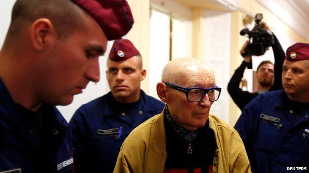Hungary's former interior minister Bela Biszku escorted by police to his trial in Budapest (13 May)