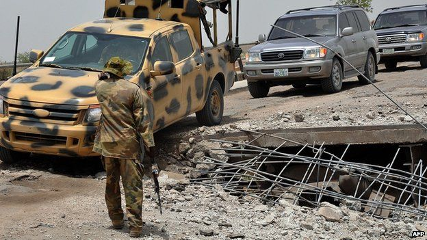 """A soldier directs the way to a military truck navigating through a link bridge at Ngala connecting Nigeria and Cameroon which was destroyed by suspected Boko Haram insurgents during last Monday""""s attack at Ngala in Gamboru"""