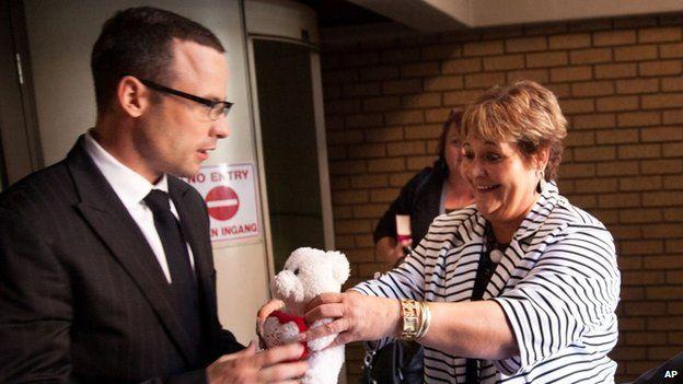 A supporter hands Oscar Pistorius a teddy bear in court